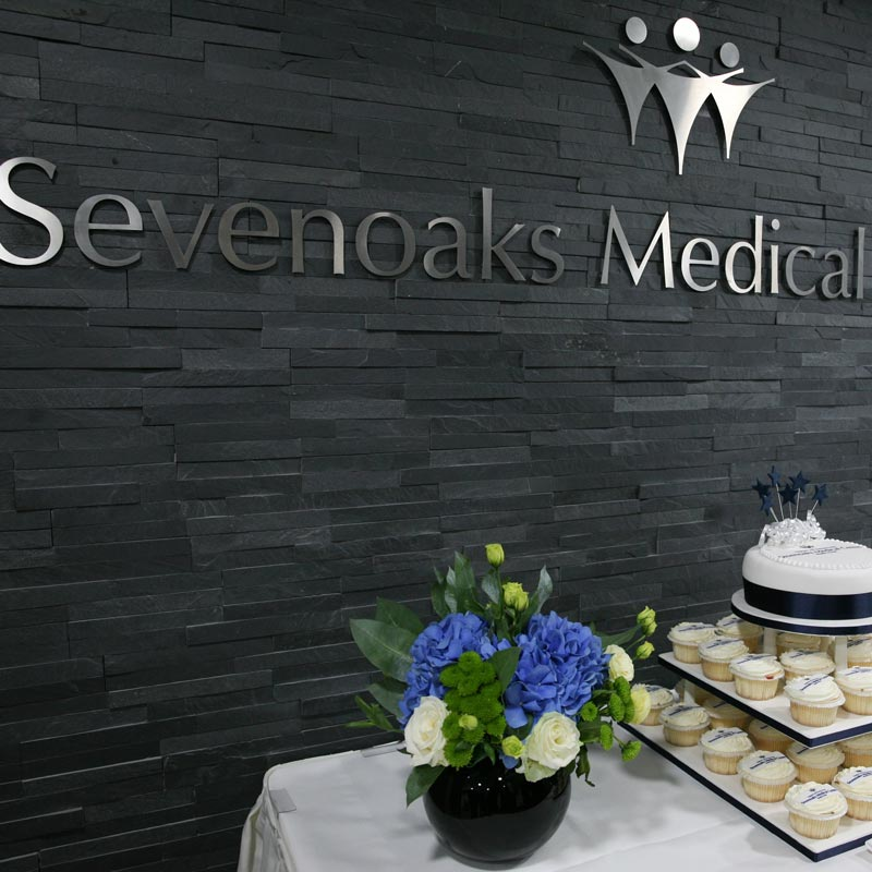 photo of Sevenoaks Medical Centre sign with flowers in vase and cupcakescake on a tiered platter
