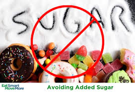 Sugary foods like sweets, cakes and doughnuts laid beside a large amount of granulated sugar which has been poured onto a table and had the word sugar drawn into it.