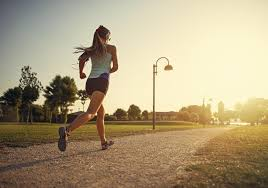 Woman in sportswear running away from the camera towards a bright sunny horizon.
