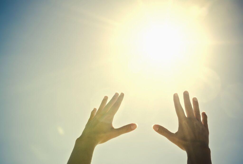 Hand reach towards the sun in the sky